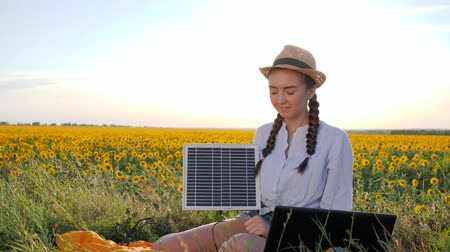 kolektor : girl shows sign approval and holds in hands solar panel in open air, female in backlight with notebook charger, young woman near solar battery and laptop on field of sunflowers Dostupné videozáznamy
