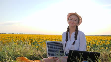kolektor : girl hold in hand solar array and shows hand gesture like using panel outdoors, female in backlight with notebook charger, young woman near solar battery and laptop on field of sunflowers