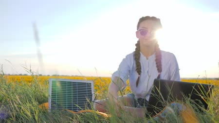 gyűjtő : female in backlight with notebook charging from sun, new technology, girl recharges laptop using solar battery on field of sunflowers, young woman applying solar photovoltaic panels outdoors