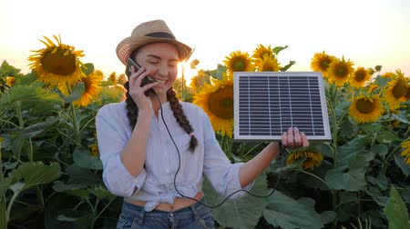 kolektor : environmentally friendly resources, girl speaks by mobile phone and holds solar panel near field of sunflowers, woman in backlit talk mobile and keep solar battery tracking sun to charge battery
