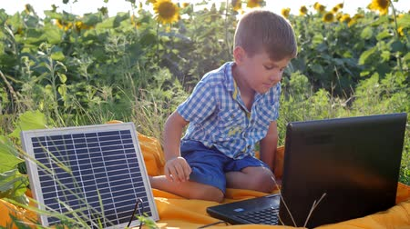 kolektor : energy-generating technology, happy child using laptop powered by solar battery on background field of sunflowers, kid looks at notebook with solar charger outdoors, modern childhood