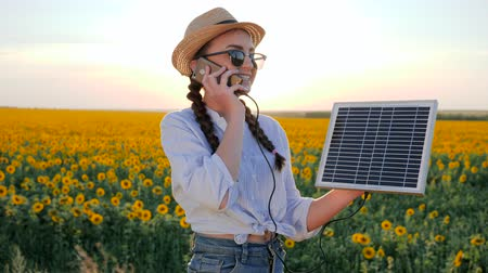 üreten : energy generation, woman talk phone and keep solar battery tracking sun to charge battery, girl speaks by mobile phone and holds solar panel in background field of sunflowers Stok Video