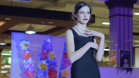 showcasing designs : Kherson, Ukraine 22 Apr. 2017: Fashion Weekend in Fabrika Mall model pose on camera during fashion show in Kherson, 22 Apr. 2017. portrait beautiful model posing in sexual black dress on catwalk, fashion week, slow motion Stock Footage
