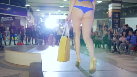 supermodel : Kherson, Ukraine 22 Apr. 2017: Fashion Weekend in Fabrika Mall fashion week, female model on high heels going at podium in bikini in Kherson, 22 Apr. 2017. sexual fashion model in swimsuit at catwalk, showcasing designs Stock Footage