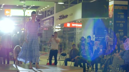 showcasing designs : Kherson, Ukraine 22 Apr. 2017: Fashion Weekend in Fabrika Mall fashion business, model in elegant clothes going along catwalk light lamps in Kherson, 22 Apr. 2017. model during fashion show on podium, slow motion