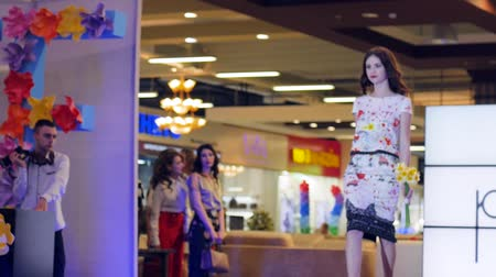 high heeled sandals : Kherson, Ukraine 22 Apr. 2017: Fashion Weekend in Fabrika Mall Model with flowers in hands on podium, fashion show of new collection of womens clothing in Kherson, 22 Apr. 2017. Defile of Stylish garments on Catwalk,