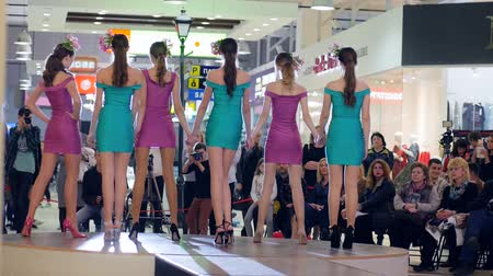 finale : Kherson, Ukraine 22 Apr. 2017: Fashion Weekend in Fabrika Mall Girls in cocktail dresses posing into front of cameras on podium, Fashion show on Catwalk in Kherson, 22 Apr. 2017. Model in high-heeled shoes and with Flowers in a hairdress, Stock Footage