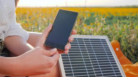 yenilenebilir : battery charger solar powered outdoor, renewable energy, close up screen cellular telephone, hands girl connects from solar panel to mobile phone outside, cell phone close-up Stok Video