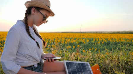 kolektor : eco, happy woman in backlight with telephone and panel in hands, girl using mobile and battery communicates in social network on background field, female browsing mobile device uses solar battery