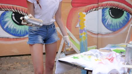 grafiti : young womans Painted clothes with spray paint on background of graffiti, design clothes of handmade outdoors, beautiful girl with cans of paint in hand, colored t-shirts painting in street style, Wideo