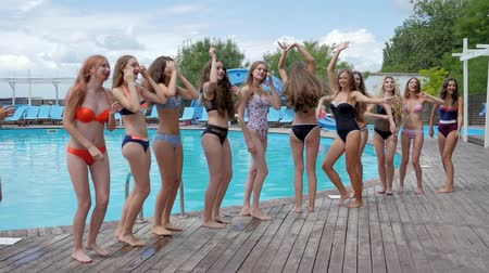 barefooted : smiling girlfriends in Swimsuit Have fun near Poolside, Crowd of woman on resort, pool party, Slender girls in bathing suits jumping near swimming pool, summer life of youth on weekend,