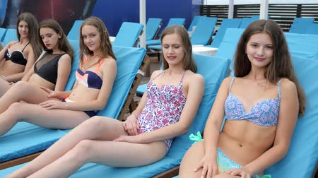 chaise longue : young women with long hair in swimsuits sitting on chaise-longue relaxes by pool, girls sit on sunlounger enjoying sun at pier, lot of female in bathing suits with beautiful legs lying on deck chair