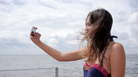 roupa de banho : girl with braces on her teeth, young female in swimsuit Photographed on mobile to waterfront ocean, Selfi of girl in bathing suit on coast sea, photo of Long-haired women on smartphone in background of water,