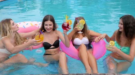 plavky : Girls with alcoholic beverage in hands are sitting in Swimming-pool, Expensive holiday at luxurious resort, Girlfriends in swimsuits on inflatable ring drink cocktails in pool,