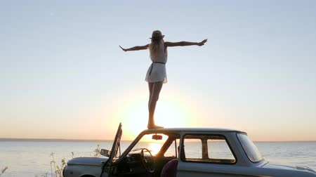 podsvícení : Happy Journey on automobile, Young woman admires sundown on Embankment, girl standing on roof Car with Widely spread hands enjoying sunset, pleasure of freedom on seafront sea, skyline,