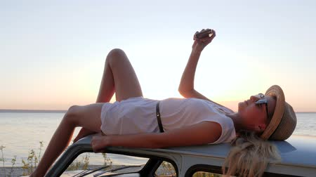 alfândega : Happy Journey, young woman lying on rooftop auto makes pictures on phone, female make selfie photo at mobile on retro car at background sea in slow motion, girl on roof car does selfi at android by sunset