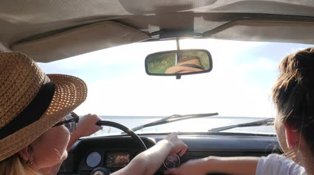 bliskosc : journey together on car, backlight, two girl spoken in automobile in sunlight, females talking into auto at background nature in slow motion, young women on summer season sitting in motor vehicle Wideo