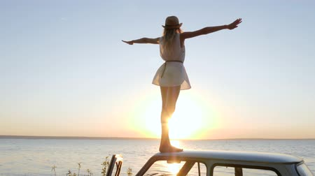 alfândega : Happy emotion Journey, girl raises arms up on roof auto outdoors in backlight, female raises arms at sunset on automobile, background sea, slow motion, woman stand on roof car, summer travel on car