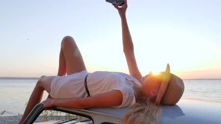 андроид : mobile phone on happy journey, Cute girl With phone into hands lies on roof of car, pictures phone do smartphone in arms girl background sunset, feminine Lying on auto Enjoying sundown to Embankment, Стоковые видеозаписи