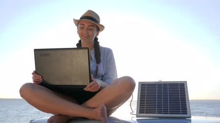 producing energy : weekend since new technology, female sitting on car rooftop with notebook and battery, background sky in backlit, happy girl sits at roof classic car with solar battery and laptop in hands Stock Footage