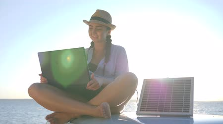 producing energy : trip, young woman sitting on car roof top with notebook and solar panel, background ocean coast in backlit, fun girl sits at roof retro car with solar battery and laptop in hands outdoors