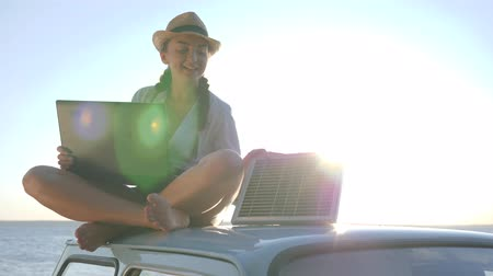 producing energy : new technology, happy girl sits on roof classic car with solar battery and laptop in hands at open air, female sitting on car rooftop with notebook and battery, background sky, backlit Stock Footage