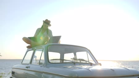 producing energy : natural energy, girl sits on roof blue classic car with solar battery and laptop in hands at open air, female sitting on car rooftop with notebook and battery, background sky in sunlight Stock Footage