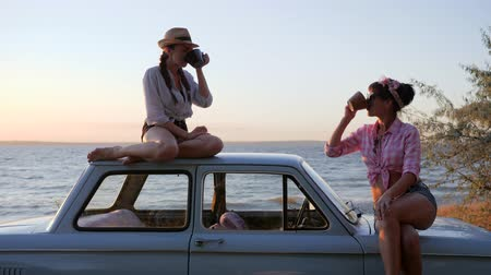 motorháztető : Girls with cups in Hands at vehicle on seafront in sundown, tea party of Friends to machine on coast sea, sunset, Lovely girlfriends drinking coffee sitting at roof and bonnet automobile,
