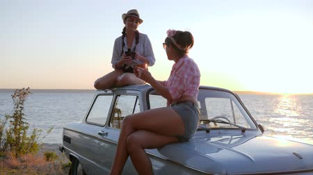 motorháztető : girlfriends drinking Tea Sitting on bonnet of auto Outdoors, Friends with cup coffee in hands to shore river on sundown, tea party of Beautiful girls to car hood at Embankment in sunset,