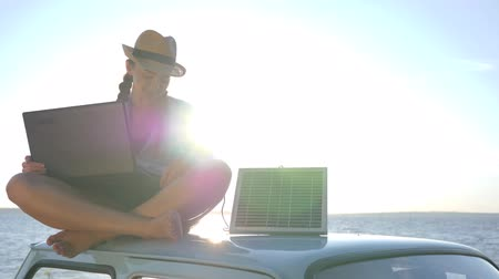 producing energy : girl sits on car roof with solar array charges laptop and waving hello in backlight, summer season, female sitting on vintage car with computer powered by battery, background blue sky in sunlight