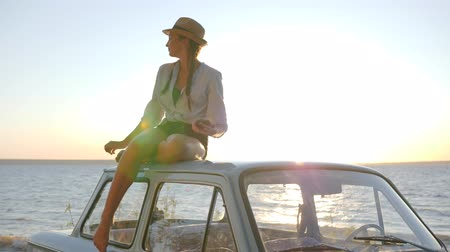 csillogás : feminine at vintage automobile, background of sunset, talk on mobile phone, Young female in old machine, Sun rays, girl On roof of Retro car near river speaks at smartphone,