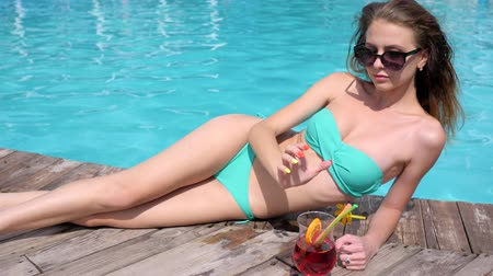 calor : sexy young woman in bikini keeps juice on hand near poolside, beautiful girl lies at wooden pier on background blue water, female relaxes with colorful cocktail beside swimming-pool Stock Footage
