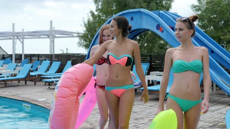 inflável : girls in bikini walking on wooden pier beside poolside with pink rubber rings, girlfriends in bathing suit with swimming circles and mattress near pool, beautiful young women on swimsuits laughing