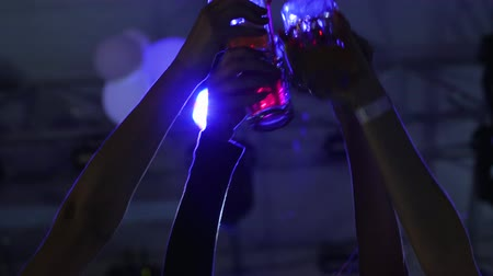 nightclub : friends raising glasses to make toast with cocktails at night club, girlfriends toasting with beverage enjoying dance on party in lumiere lights, happy women do toasts and dancing at night party Stock Footage