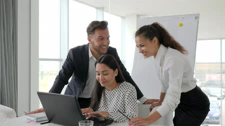 spolupracovníci : young successful people, successful deal business team in modern office, emotional employees in office, multi ethnic group of people working over computer screen, managers is happy Dostupné videozáznamy
