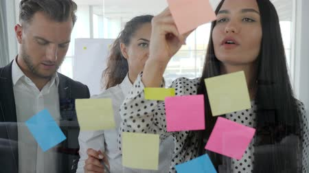 each other : young business team writing down ideas on sticky notes attached to glass wall, office people watching at colorful stickers, brainstorming, workers looking at glass wall planner with notes in boardro Stock Footage