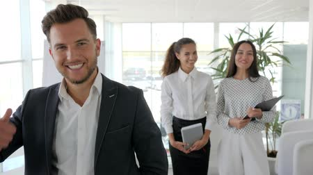 multinational : Smiling mentor stand with office workers in Business center, Executive giving thumbs up on background business team in office, positive gesture of boss close-up with group collaborators at work, Stock Footage