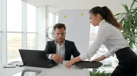 mentor : secretary Prepares coffee for boss in Business center, executive Gives documentation From hand to hand of employee, Serious businessman Works on laptop in modern office,