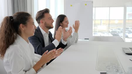 spolupracovníci : managers smile and clap at Table in business center, happy business group clapping hands in slow motion, employees applaud at office, colleagues near desk on conference meeting