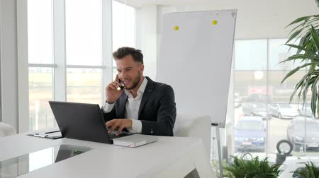 munkatárs : happy executive talk on smartphone at workplace in Business center, phone conversation of young boss in modern office, Successful businessman Works on laptop at Internet on boardroom, Stock mozgókép