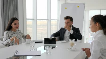 spolupracovníci : director and employees at break, coffee-break in office, business people drink coffee at table, creative team drinking hot drinks from cup on background white and spacious office Dostupné videozáznamy