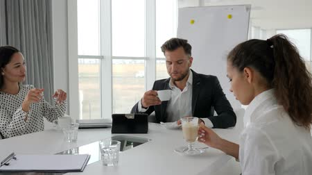 spolupracovníci : coffee-break in office, business people drink coffee at table, director and employees at break, creative team drinking hot drinks from cup on background white and spacious office