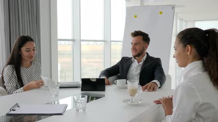 spolupracovníci : business people drink coffee at table, director and employees at break, creative team drinking hot drinks from cup on background white and spacious office, coffee-break in office