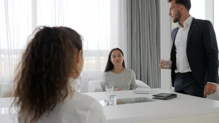 spolupracovníci : aggressive director and female employees at table in office, evil boss hold in hand glass water on conference room, business people at background white and spacious office