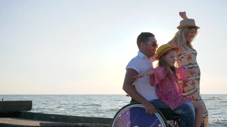 deficientes : invalid at summer, family play together on background blue sky, little girl sitting on daddy in wheelchair with outstretched arms in backlight, disabled man with pregnant wife and daughter spinning hands Stock Footage