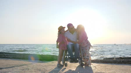 alfândega : Rest, Invalid With wife and daughter in backlight, dad, child mother hugging each other, joyful family on background sea, man in wheelchair with little girl and pregnant woman outdoors