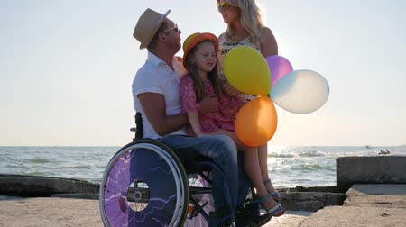 cripple : lover disabled with family, handicapped parents with child, daughter sitting on dad with balloons in hand, pregnant woman, handicapped person on sea, mom and daughter hugging father in backlight Stock Footage