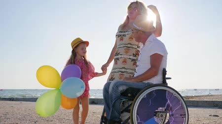 alfândega : parents tell of maternity, disabled person in wheelchair with family, little girl listens mother and father on wheel chair at beach in summer, happy mom and daughter stand near dad invalid at backlight