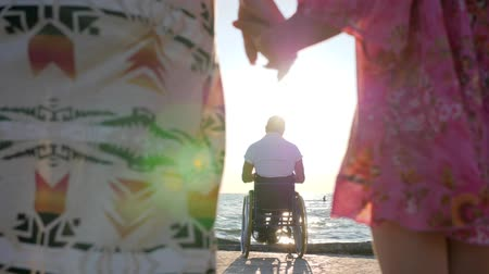 alfândega : disabled man on wheelchair with family, mother and daughter keep hands on background father sitting in wheelchairs, love with disabled person, family outdoors, summer time, girl and mom holding hands Stock Footage