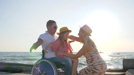inwalida : little girl sitting on hands paralyzed daddy in wheelchair with outstretched arms in backlight pregnant wife with child and disabled men experience happy emotions on summer vacation.